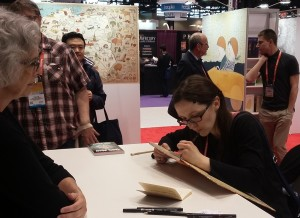 Illustrator Aleksandra Mizieliski signs a copy of Maps.